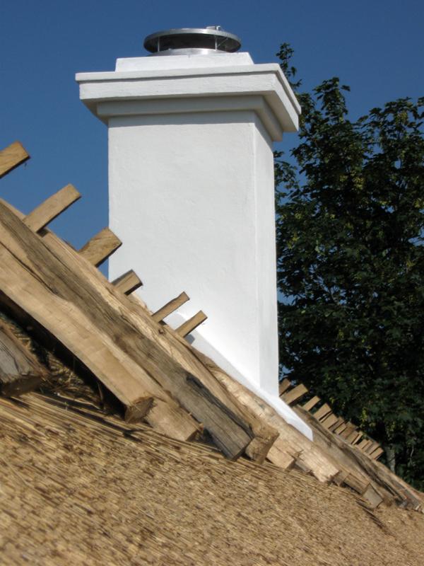 Vitputsad skorsten och korslagda ekträn över taknocken